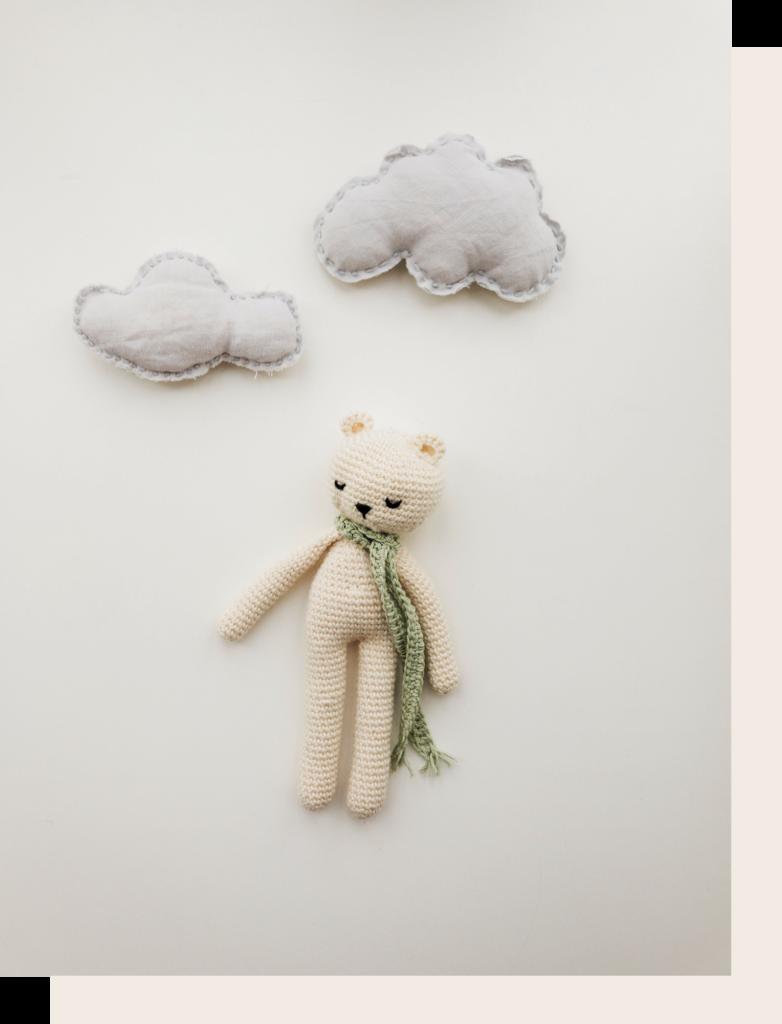 Oso de ganchillo blanco y nubes de fieltro gris.